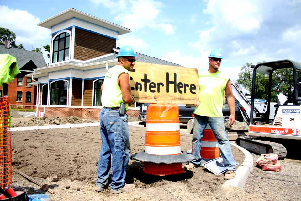 The Bank of Cooperstown's Oneonta branch is beginning to take shape on Main Street, across from the River Street intersection.  Here, Steve Conklin, left, of Laurens and Dan Finny of Davenport shift signage at the end of today's shift.  The branch -- its design is modeled after an old-train depot, reflecting Oneonta's history -- is due to open in September.  (Jim Kevlin/AllOTSEGO.com)