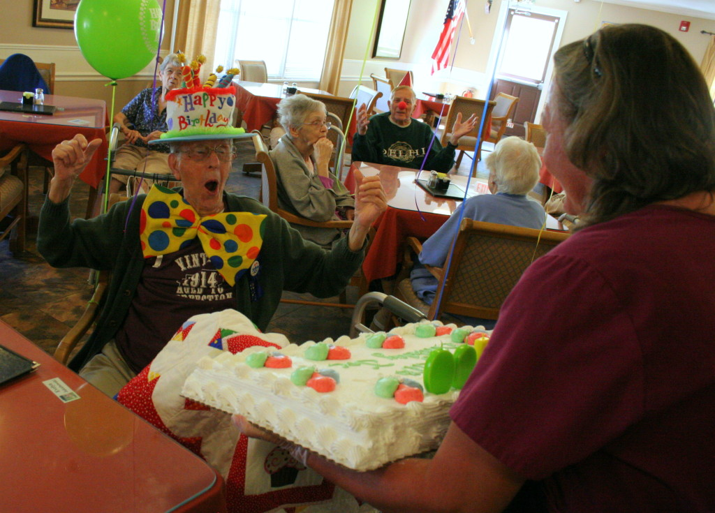 Think you are too old for a clown themed birthday party? Think again! Joe Libutti, left, a resident at the Hapshire House Adult Home in Oneonta, whoops for joy as his birthday cake is brought out by Lori Gordnough, Morris, to celebrate his 100th birthday.  One of Joes' many careers throughout his century of life was as a clown, so red noses and  polka-dotted birthday were a welcome surprise from the staff.