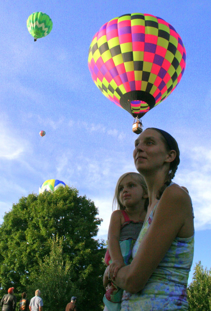 The 2014 Susquehanna Balloon Glow kicked off Friday evening with balloon launches and rides beginning at 6pm. Balloons took off from the former softball fields in Neahwa Park, flew over the park and landed in the nearby soccer field. Here, Liz Brown, Oneonta, holds her daughter Keira as the balloons fly overhead.
