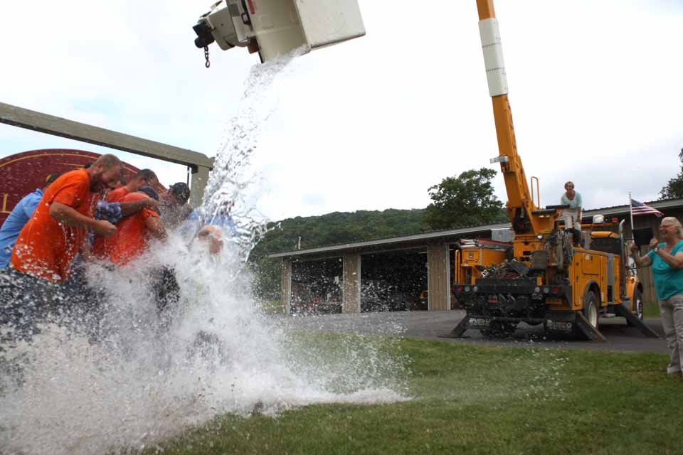 A backload bucket full of icey water is poured down on Otsego Electric Cooperative President Steve Rinell and his crew this afternoon, part of the ALS Challenge.  (Jim Kevlin/AllOTSEGO.com)