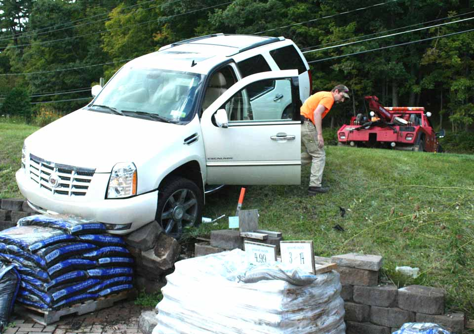 Tyler Miles of Kirn's Body Shop prepares to haul a Cadillac Escalade out of the nursery department at Haggerty ACE Hardware, Cooperstown.  The auto had rolled down the hill from the Church & Scott parking lot shortly before noon today.  (Jim Kevlin/AllOTSEGO.com)