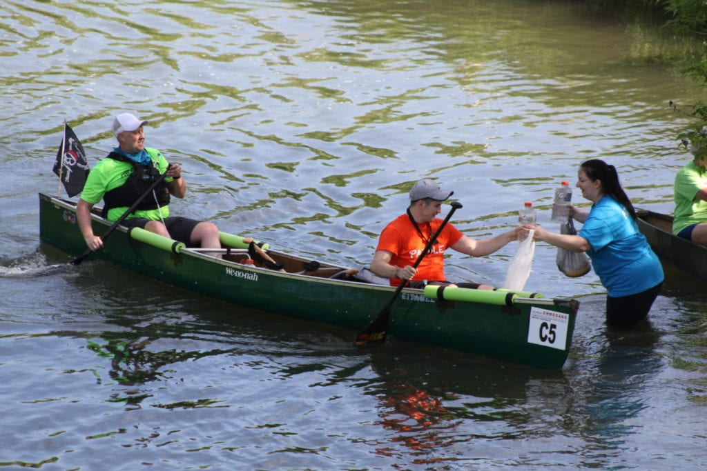 Cindy MiHeager, Cooperstown, hands bags of snacks and fresh bottles of water to John Bugyi and Mike Silicato, Morris, as they paddle down the Susquehanna Rvier as part of the annual General Clinton Canoe Regatta. (Ian Austin/AllOTSEGO.com)
