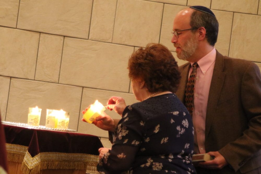 Ken Sider, President of Temple Beth El in Oneonta, lights a ceremonial candle alongside Regina Betts, a Holocaust survivor, during a Holocaust Martyrs' and Heroes' Remembrance service this evening at the synagogue. Six candles were lit for the 6 million who died. (Ian Austin/AllOTSEGO.com)