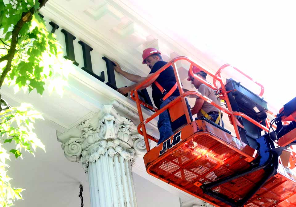 Mike DiNigro, left, and Fadfil Pucvarevic install the letters on the front of Cooperstown Village Hall this morning as renovations to the historic building continue. Both are with National Building & Restoration, Utica. A $190,000 project is repairing the Corinthian pillars and their footings on the front porch, stabilize the facade and repainting the front of the building, reporting Village Trustee Lou Allstadt, who was on the scene this morning observing the sign's installation. (Jim Kevlin/AllOTSEGO.com)