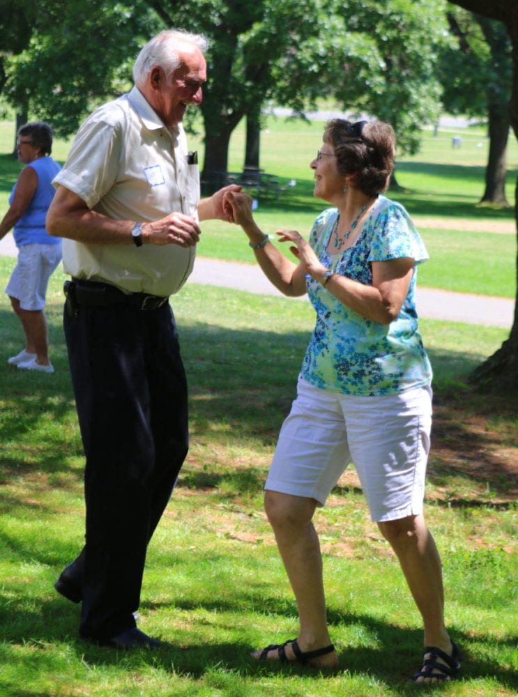 """Carolyn Elwell and Art Henry, both of Goodyear Lake, dance together as Jim Dorn sings """"Wagon Wheel"""" by Bob Dylan at the Senior Picnic at Glimmerglass State Park this afternoon. The event featured information sessions on opportunities for seniors, music, lunch, raffles and bingo. (Ian Austin/AllOTSEGO.com)"""