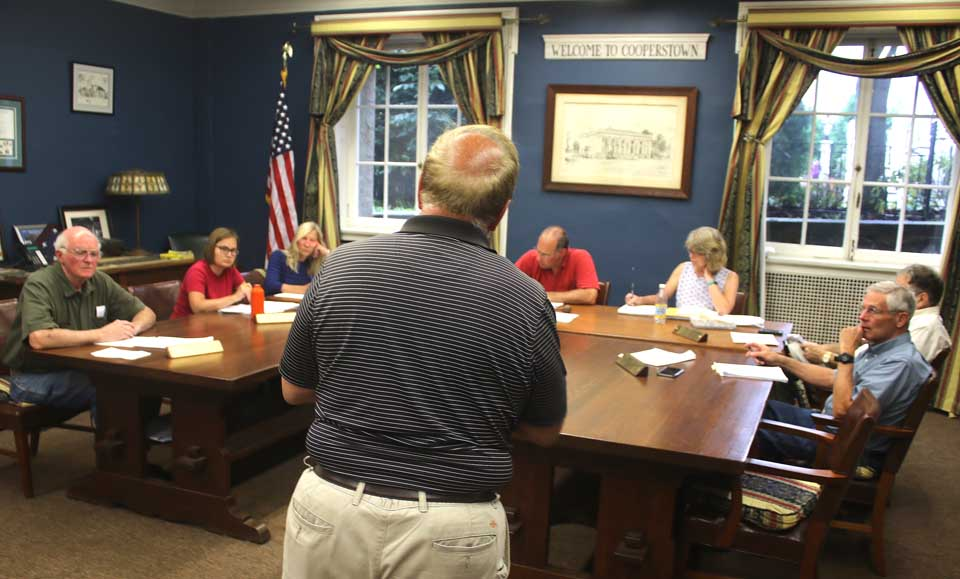 """Vin Russo, Mickey's Place proprietor, (back to camera), suggests to the Cooperstown Village Board at this evening meeting that it form an """"entity"""" to interface with the Hall of Fame over issues that rose during this Induction Weekend, then to do so again in advance of future Inductions. """"There were a lot of things that did come up,"""" said Russo. """"While it is fresh in our minds, I think we should discuss what we might do about it."""" One current issue is the metal fences the Hall installs along Main Street, how close they should be to the curbs and whether there are sufficient breaks for people to cross the street. Further, Russo said, often people don't know where to raise questions, with Village Hall, the Baseball Hall, police or whatever. After he departed, Trustee Cindy Falk said, """"I think Vinnie's idea is a good one."""" Mayor Jeff Katz assigned the question to Falk's Economic Development Committee, with perhaps forming such an entity during August. Seated, from left, are Trustees Jim Dean, Falk and Ellen Tillapaugh Kuch, Village Attorney Martin Tillapaugh, Mayor Katz, Village Clerk Teri Barown, and Trustees Richard Sternberg and Lou Allstadt. (Jim Kevlin/AllOTSEGO.com)"""