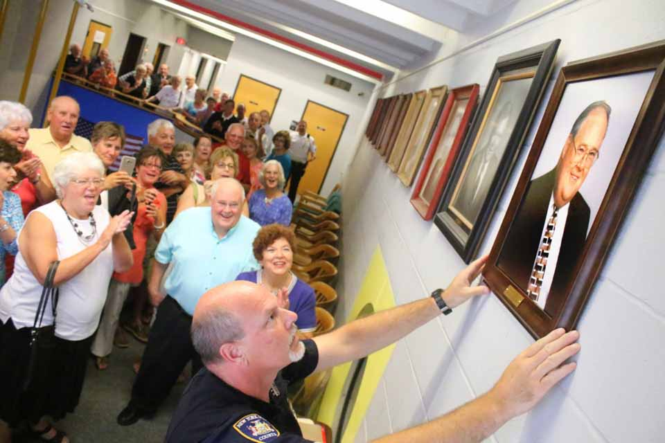 State Court Officer Matthew Brown hangs the official portrait of former Oneonta City Judge Walter Terry III, seen behind him with wife Diane, in the City Court hallway this afternoon in the city's Public Safety Complex at Main and Market.   Family and friends attended to celebrate the event. County Judge Brian Burns, City Judges Richard McVinney and Lucy Bernier and Chief City Courty Clerk Cathy Tisenchek delivered remarks praising Judge Terry's character, ethics, respect, fairness and temperament.  Judge Terry served on the city bench from 1999 to 2008, then resumed private practice. (Ian Austin/AllOTSEGO.com)