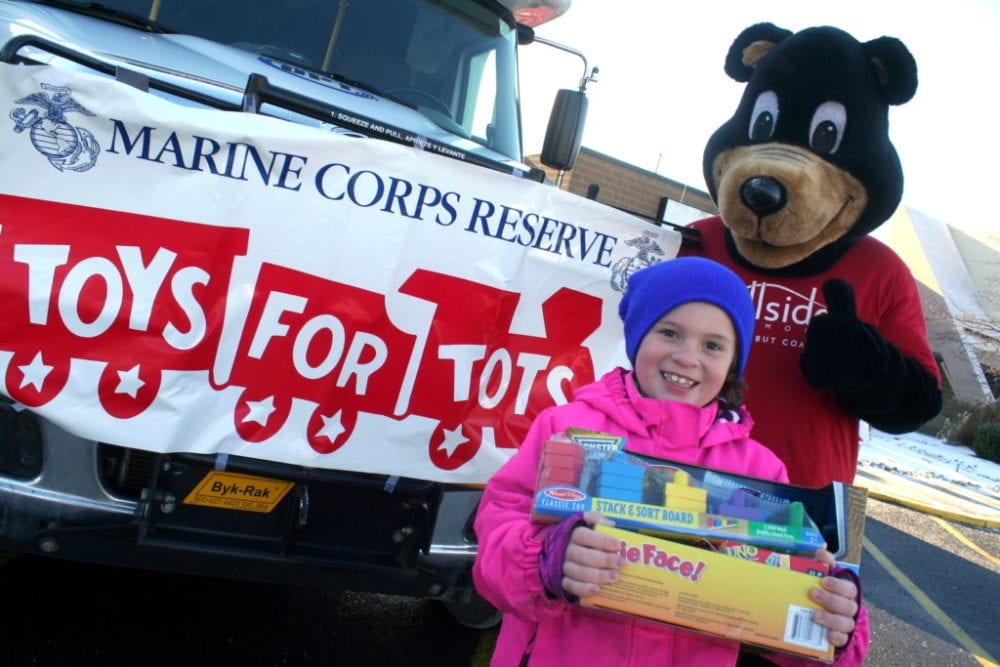 """It is a chilly morning, but that didn't keep Desiree Wheeler and the Hillside Commons Bear from standing outside the annual Fill The Bus event to benefit Toys For Tots Drive at the Southside Mall this morning. The bus, provided by OPT in conjuction with Hillside Commons, will be at the mall from 9am-11am on Saturday. Toys can still be dropped off at many locations around town before they are collected on December 14th. """"I didn't get a lot of toys this year."""" said organizer Sharron Wheeler, """"I am still about 700 toys short. I hope our County can step up to help the kids this Holiday season."""" If you would like more information, or, to drop off toy donations, call 607.432.7052. (Ian Austin/AllOTSEGO.com)"""