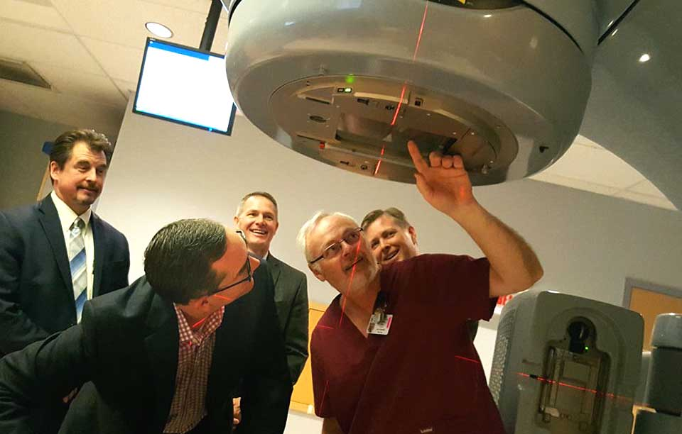 """Mark Tryniski, left, Community Bank president/CEO, and Radiation Therapist Roy Doremus, right, look into the eye of the Foxcare Cancer Treatment Center's linear accelerator. Tryniski was at FoxCare todayto deliver the final $20,000 payment of a $100,000 pledge the bank made toward the 2012 purchase of the advanced apparatus, which more accurately pinpoints tumors and treats them, avoiding the need for more intense radiation. Behind them are, from left, Jeff Lord, Commercial Banking team leader, Joe Sutaris, bank vice president, and Jeff Joyner, Fox Hospital president.  """"These cutting-edge treatments are changing the landscape of cancer treatment, making radiation therapy an open for many more patients than ever before,"""" said Joyner.  He also thanked the Dewar and Robinson Broadhurst foundation for helping cover the accelerator's price. (Ian Austin/AllOTSEGO.com)"""